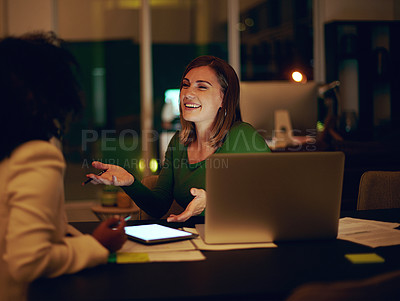 Buy stock photo Shot of two businesswomen working together in an office at night