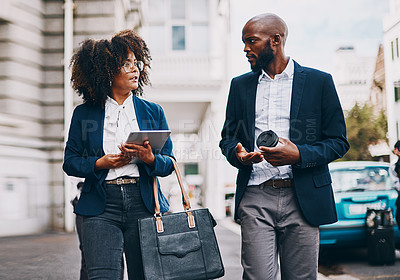 Buy stock photo Shot of two businesspeople having a discussion while walking through the city together