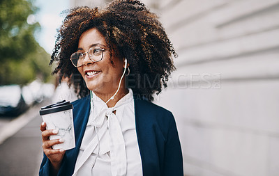 Buy stock photo Shot of a businesswoman holding a coffee and listening to music through earphones while walking through the city