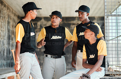 Buy stock photo Shot of a group of young baseball players chatting while standing in the dugout