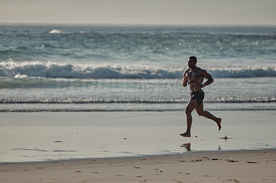 Buy stock photo Shot of a muscular young man running at the beach
