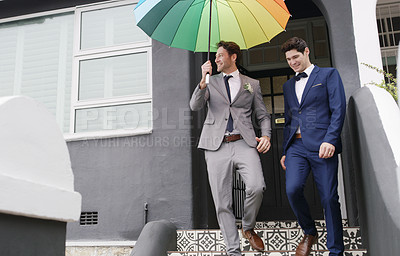 Buy stock photo Shot of two men walking with a colourful umbrella on their wedding day