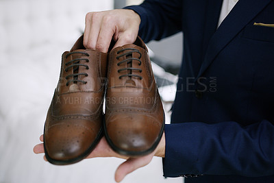 Buy stock photo Cropped shot of a groom holding up his shoes