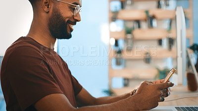 Buy stock photo Shot of a young designer using a cellphone in an office
