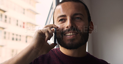 Buy stock photo Shot of a young man talking on a cellphone at home