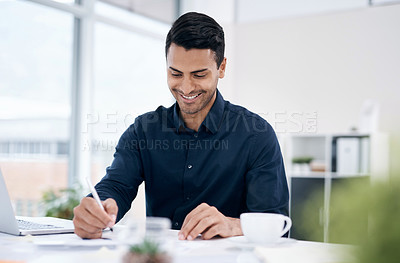 Buy stock photo Shot of a young businessman going through paperwork at his desk in a modern office