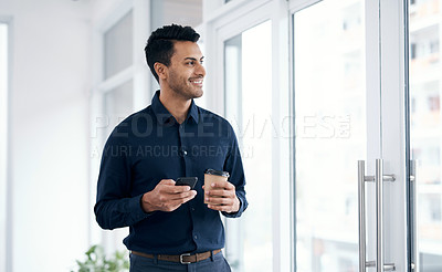 Buy stock photo Shot of a young businessman having coffee and using a smartphone in a modern office