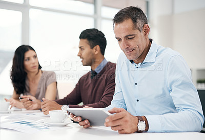 Buy stock photo Shot of a businessman using a digital tablet during a meeting in a modern office
