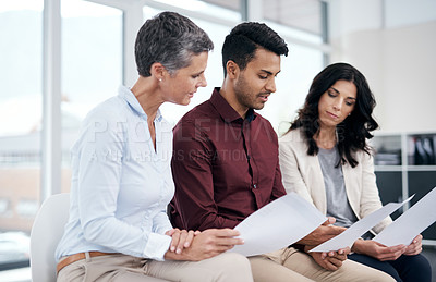 Buy stock photo Shot of a group of businesspeople going over paperwork in a modern office