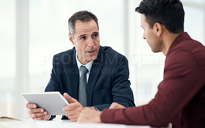 Buy stock photo Shot of two businessmen using a digital tablet in a modern office