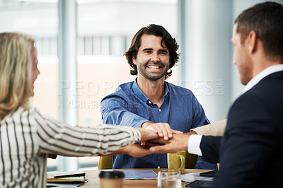 Buy stock photo Shot of a group of businesspeople joining hands during a meeting in a modern office