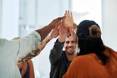Buy stock photo Shot of a group of young businesspeople joining their hands in solidarity in a modern office