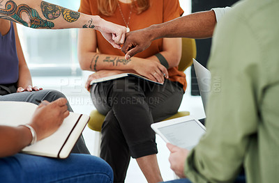 Buy stock photo Cropped shot of a businesswoman and businessman fist bumping during a team meeting in a modern office