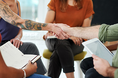 Buy stock photo Cropped shot of a businesswoman and businessman shaking hands during a team meeting in a modern office