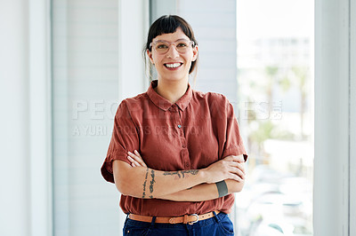 Buy stock photo Cropped shot of a confident businesswoman standing with her arms crossed in an office