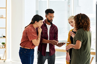 Buy stock photo Cropped shot of a group of businesspeople discussing something on a digital tablet