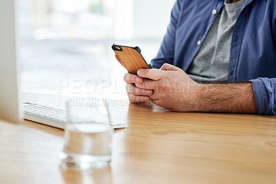 Buy stock photo Cropped shot of a businessman using his cellphone while sitting at his desk