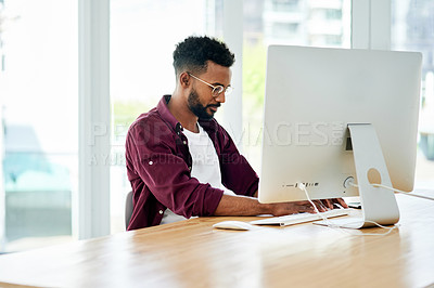 Buy stock photo Cropped shot of a businessman using his computer while sitting at his desk