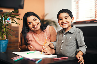 Buy stock photo Portrait of an adorable little boy colouring in with his mother at home