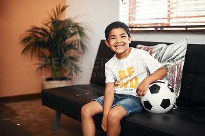 Buy stock photo Portrait of an adorable little boy sitting with a soccer ball on the sofa at home