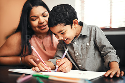 Buy stock photo Shot of an adorable little boy colouring in with his mother at home
