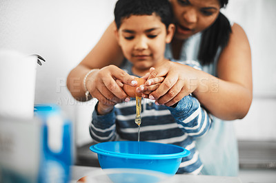 Buy stock photo Shot of a mother and her little son cracking an egg together while baking at home