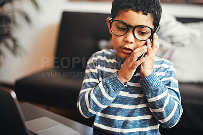 Buy stock photo Shot of an adorable little boy talking on a cellphone while using a laptop at home