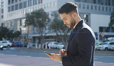 Buy stock photo Shot of a young businessman using a smartphone against a city background
