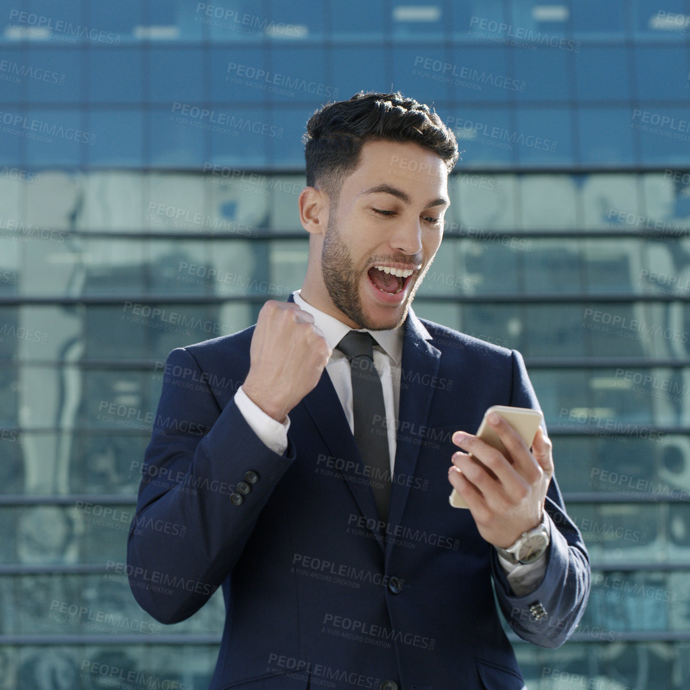 Buy stock photo Shot of a young businessman using a smartphone and celebrating good news against an urban background