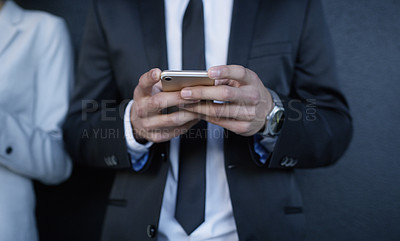 Buy stock photo Shot of an unrecognisable businessman standing against a wall outdoors and using his smartphone