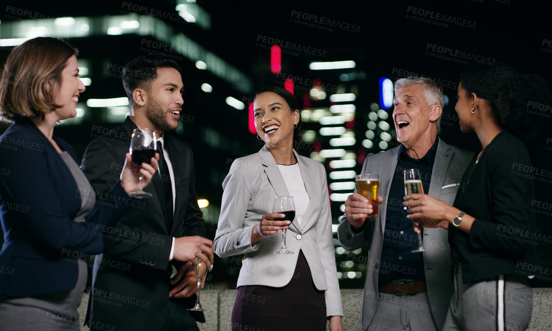 Buy stock photo Shot of a group of businesspeople having drinks after work in the city at night