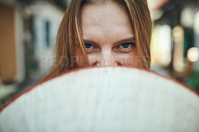 Buy stock photo Cropped shot of a woman holding a conical hat in front of her face
