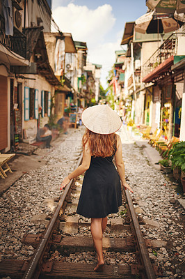 Buy stock photo Shot of a young woman wearing a conical hat while exploring a foreign city