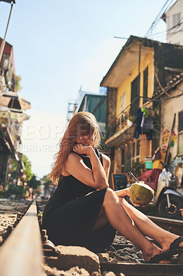 Buy stock photo Shot of a woman having coconut water while relaxing on the train tracks in the streets of Vietnam