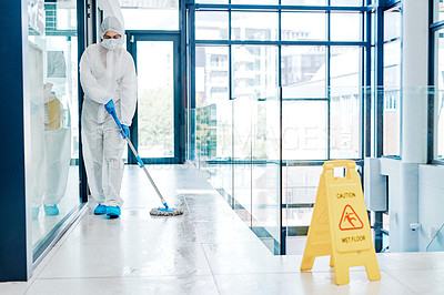 Buy stock photo Shot of a young woman wearing a hazmat suit while sanitising a building