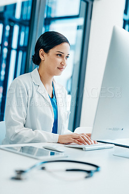 Buy stock photo Shot of a young doctor working on a computer