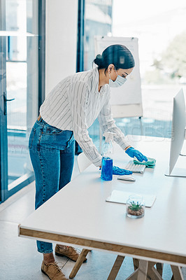 Buy stock photo Shot of a young businesswoman cleaning her workspace in an office
