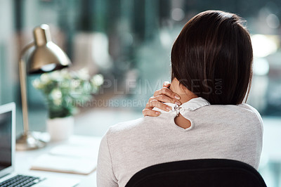 Buy stock photo Rearview shot of a young businesswoman experiencing neck pain while working in an office