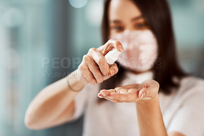 Buy stock photo Closeup shot of a businesswoman using hand sanitiser in an office
