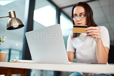 Buy stock photo Shot of a young businesswoman using a laptop and credit card in an office