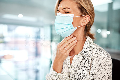 Buy stock photo Shot of a mature businesswoman wearing a mask and rubbing her throat in an office