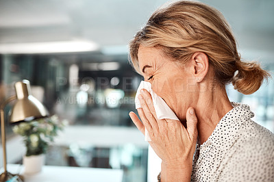 Buy stock photo Shot of a mature businesswoman blowing her nose while working in an office