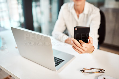 Buy stock photo Closeup shot of an unrecognisable businesswoman using a cellphone and laptop in an office