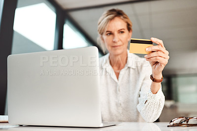 Buy stock photo Shot of a mature businesswoman using a laptop and credit card in an office