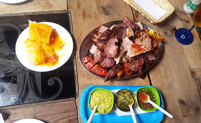 Buy stock photo Shot of various cuts of grilled meat served with condiments on a table