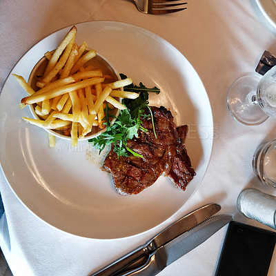 Buy stock photo Shot of a juicy cut of grass fed steak and fries served on a plate in a restaurant