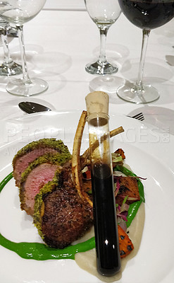 Buy stock photo Shot of a rack of lamb served a test tube filled with sauce at a one dining restaurant