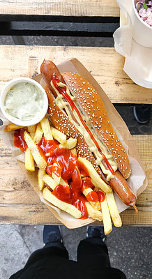Buy stock photo Cropped shot of a man having a freshly made hot dog with french fries in Bratislava, Slovakia