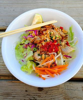 Buy stock photo Shot of a healthy salad in a bowl served with chopsticks on a table at a restaurant