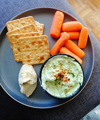 Buy stock photo Shot of crackers served with carrots and dip on a plate